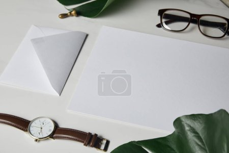 Letter template with glasses and watch on white marble background with monstera leaves