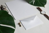Business mock up set with envelope and watch on white marble background with monstera leaves