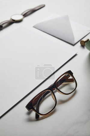 Composition with envelope and glasses on white marble background