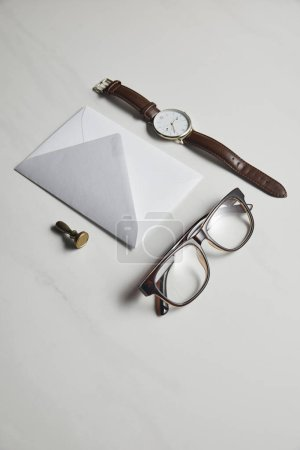 Stationery template with watch and glasses on white marble background
