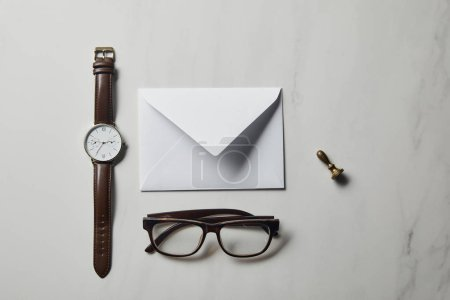 Letter template with glasses and watch on white marble background
