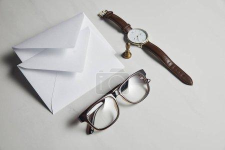 Enveloppe de blanc avec des lunettes et montre sur fond de marbre blanc