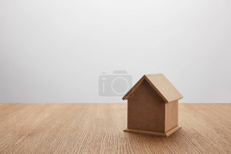 Photo for Close-up view of small house model on wooden table on grey, insurance concept - Royalty Free Image