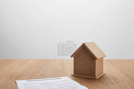 close-up view of insurance form and small house model on wooden table on grey