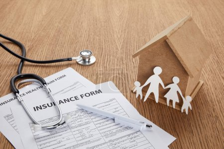 close-up view of insurance form, insurance health claim form, pen, stethoscope, house model and paper cut family on wooden table