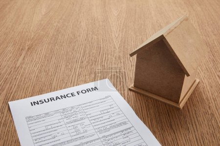 close-up view of insurance form and small house model on wooden table with copy space