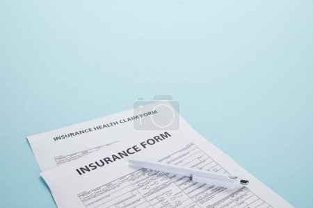 close-up view of insurance form, insurance health claim form and pen isolated on blue