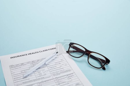 close-up view of insurance health claim form, pen and eyeglasses on blue