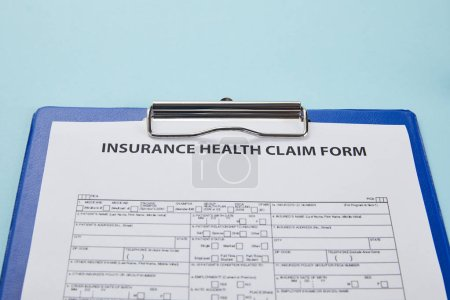 close-up view of insurance health claim form on clipboard isolated on blue