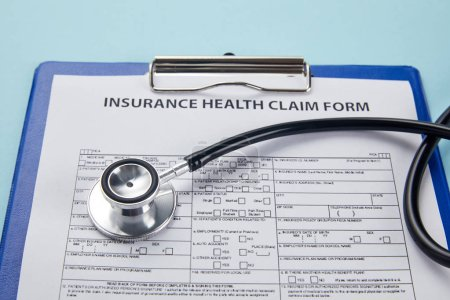 close-up view of insurance health claim form on clipboard and stethoscope on blue