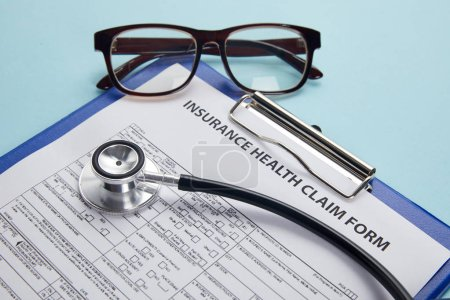 insurance health claim form, clipboard, eyeglasses and stethoscope on blue