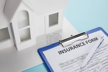 close-up view of insurance form and small house model with clipboard and pen on blue