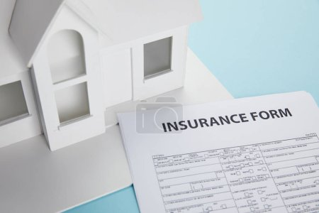 close-up view of insurance form and small house model on blue