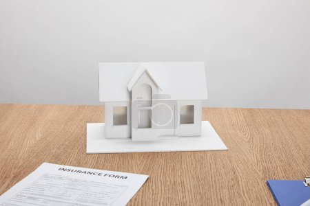 close-up view of insurance form and small house model on wooden table