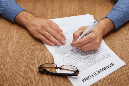 cropped shot of person signing insurance form at wooden table with eyeglasses