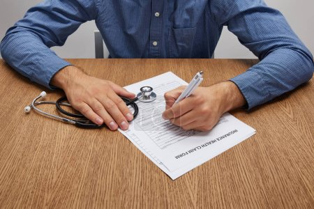 cropped shot of person holding stethoscope and signing insurance form at wooden table