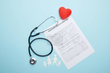 top view of stethoscope, insurance health claim form, red heart symbol and paper cut family isolated on blue