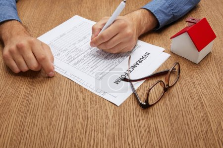 cropped shot of person signing insurance form at wooden table