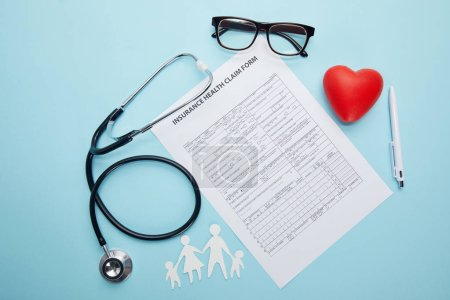 top view of insurance health claim form, eyeglasses, paper cut family, red heart symbol and stethoscope on blue
