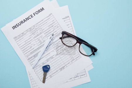 top view of insurance form, eyeglasses, key and pen isolated on blue