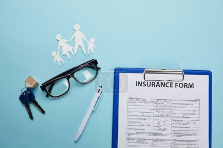 top view of insurance form, eyeglasses, pen, paper cut family and keys isolated on blue