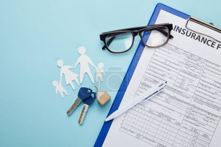 top view of insurance form, pen, paper cut family and keys isolated on blue