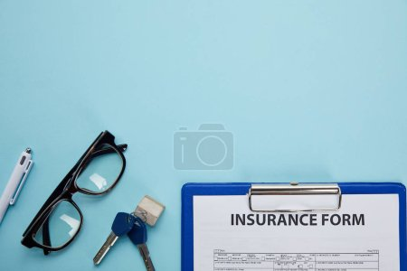 close-up view of insurance form, eyeglasses, pen and keys isolated on blue