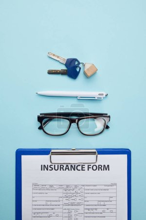 top view of insurance form, eyeglasses, pen and keys isolated on blue
