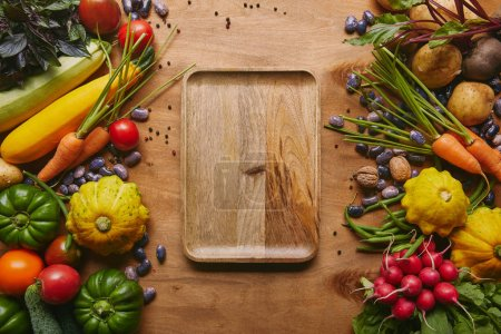 Photo for Organic raw vegetables with tray on wooden table - Royalty Free Image