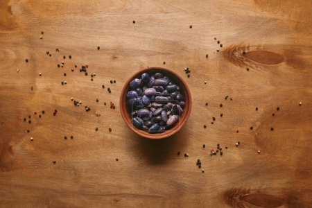 Dry haricot beans in bowl with pepper on wooden table