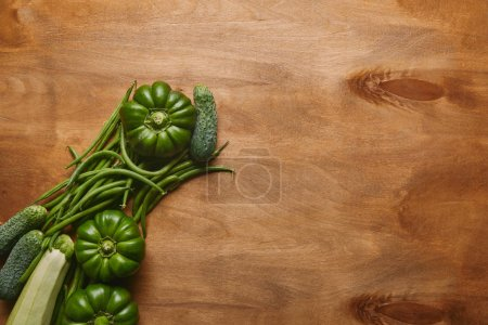 Bell peppers and green beans on wooden table