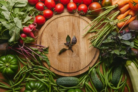 Photo for Variety of fresh vegetables and herbs by cutting board on wooden table - Royalty Free Image