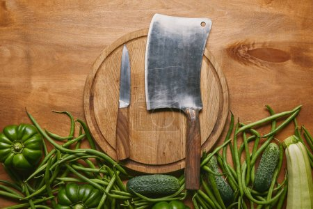 Photo for Cleaver and smaller knife on cutting board with green vegetables on wooden table - Royalty Free Image