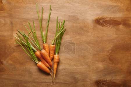 Bunch of raw carrots on wooden table
