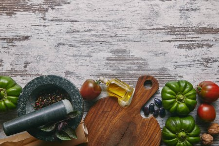 Vegetables and condiments in mortar on rustic wooden table