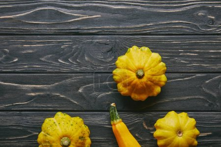 Yellow summer squashes on dark wooden table
