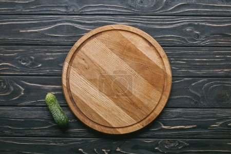 Photo for Cutting board and cucumber on dark wooden table - Royalty Free Image