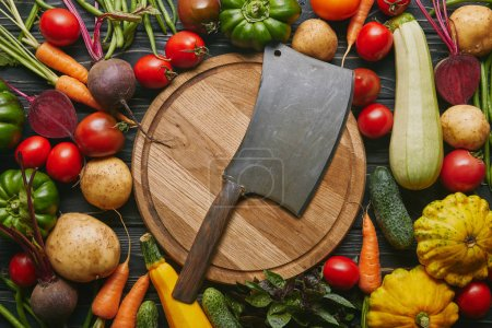 Metal cleaver on cutting board with colorful vegetables on dark wooden table