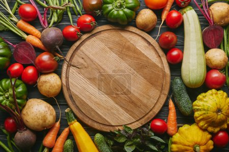 Variety of colorful vegetables by cutting board on dark wooden table