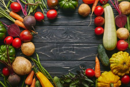 Frame of healthy summer vegetables on dark wooden table