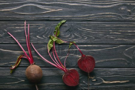Small red beetroots on dark wooden table