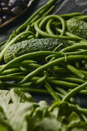 Cucumber and green beans on dark wooden table
