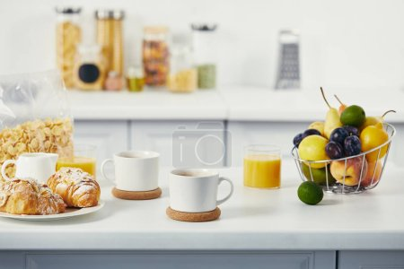 Photo for Close up view of cups of coffee and croissants for breakfast on white tabletop in kitchen - Royalty Free Image