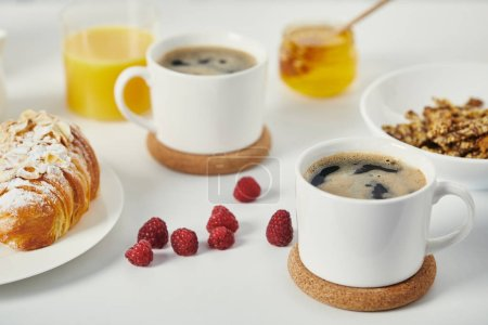 Photo for Close up view of tasty breakfast with cups of coffee and croissant on white surface - Royalty Free Image
