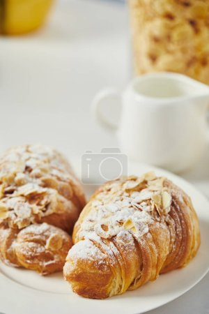 Photo for Close up view of sweet croissants with sugar powder for breakfast on white tabletop - Royalty Free Image