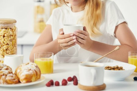 partial view of woman with cup of coffee having breakfast at home
