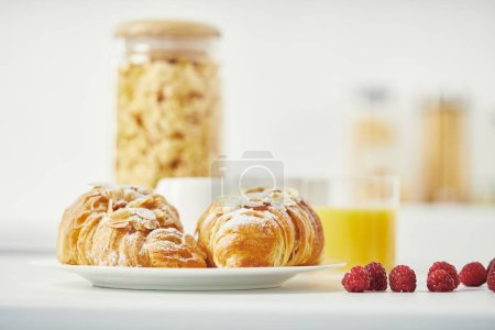 Photo for Close up view of freshly baked croissants and raspberries for breakfast on white surface - Royalty Free Image