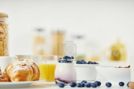close up view of healthy yogurt with fresh blueberries and croissant for breakfast on white tabletop