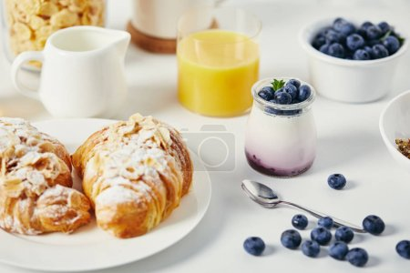 close up view of healthy yogurt with fresh blueberries and croissants for breakfast on white tabletop