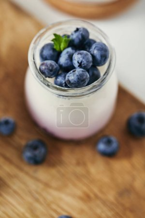 close up view of yogurt with fresh blueberries for breakfast on wooden cutting board